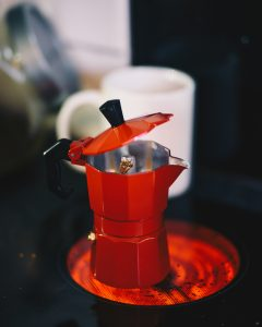 red moka pot open lid on hot stove with coffee cup in background